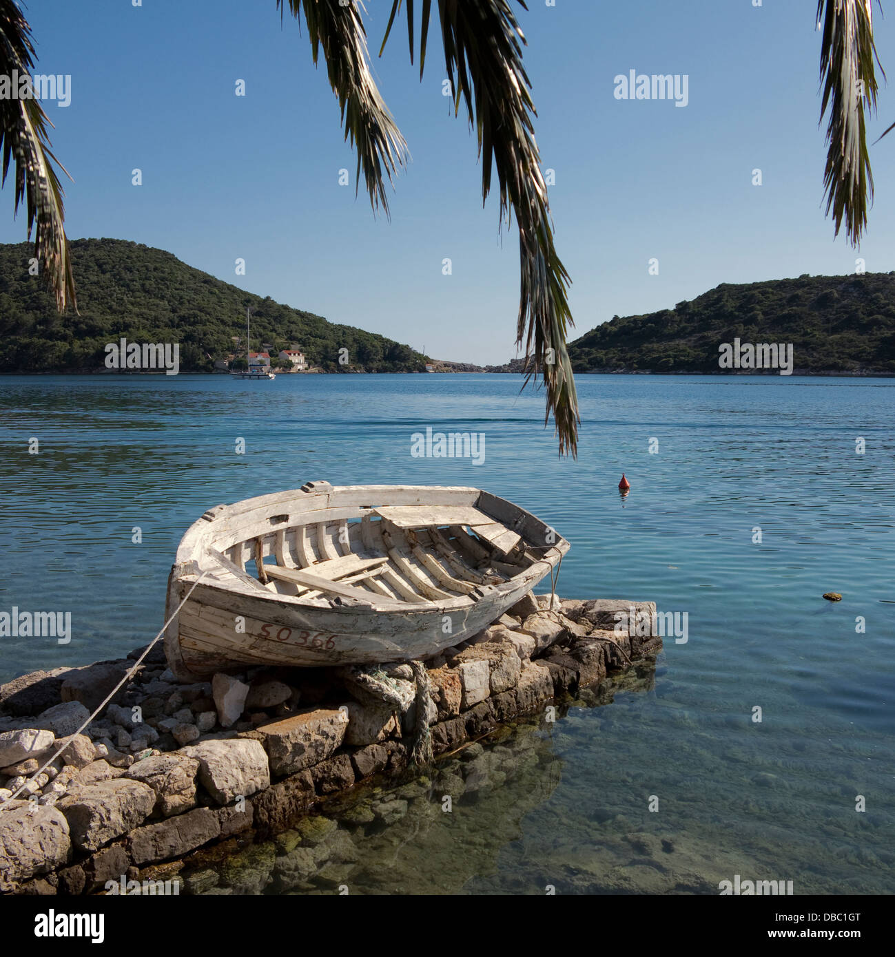 old white rowing boat by a bay on island of Sipan on the Dalmatian coast, near Dubrovnik, Croatia - Stock Image