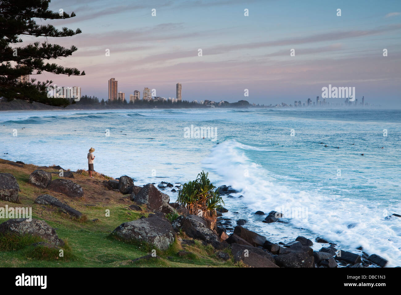 Man watching surfers at Burley Heads, at dawn. Gold Coast, Queensland, Australia - Stock Image