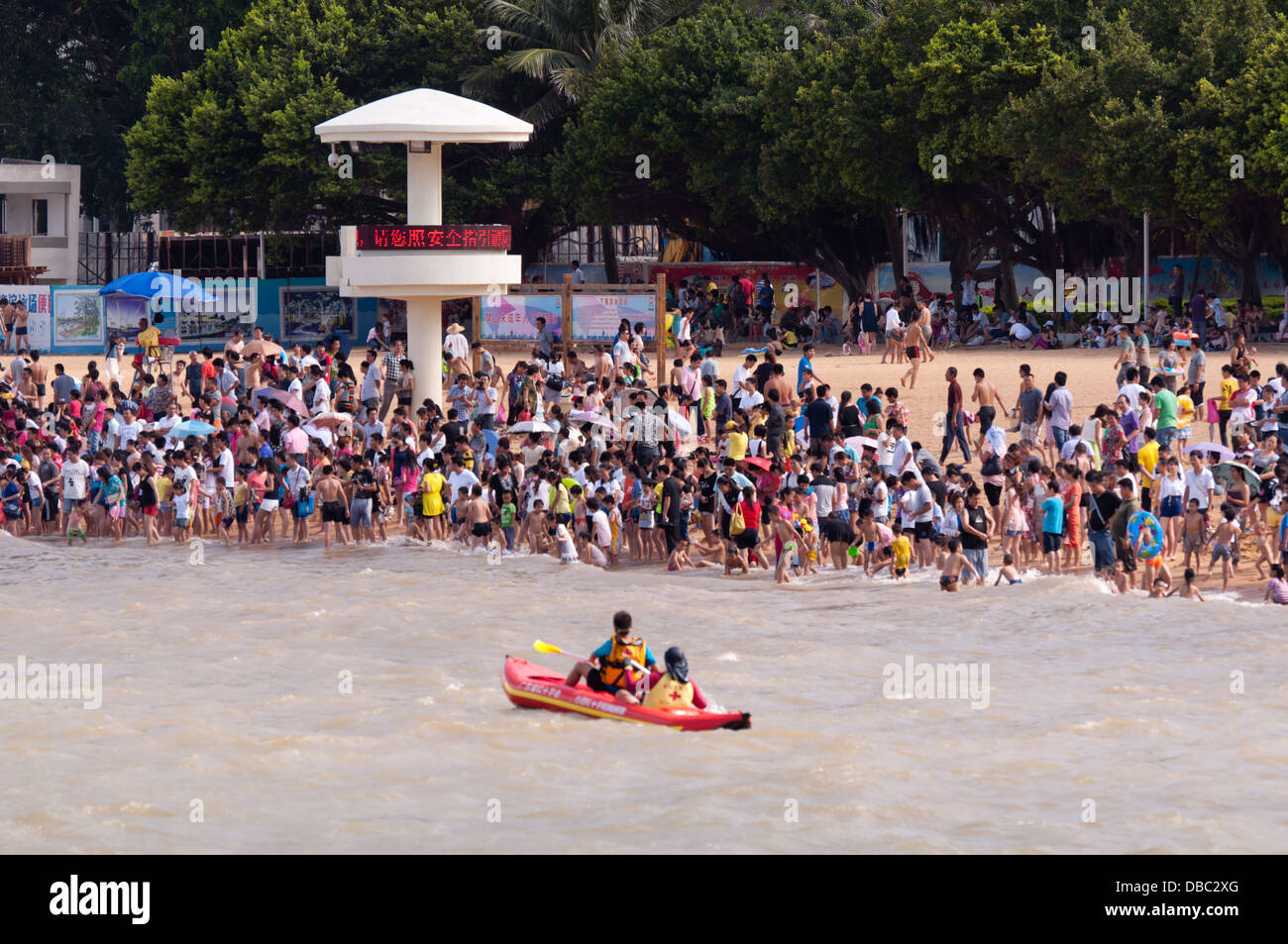 Crowd people at hot summer swimming at the beach in Zhuhai, China - Stock Image