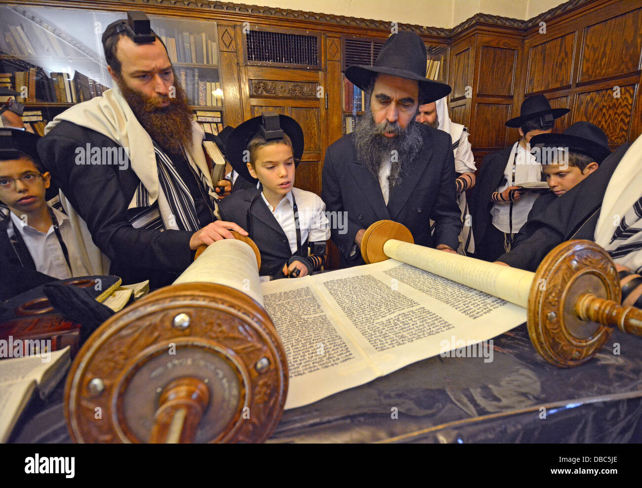 Religious Jews pray in the Rebbe's study at Lubavitch Headquarters in Brooklyn, New York. Bar Mitzvah boy called - Stock Image
