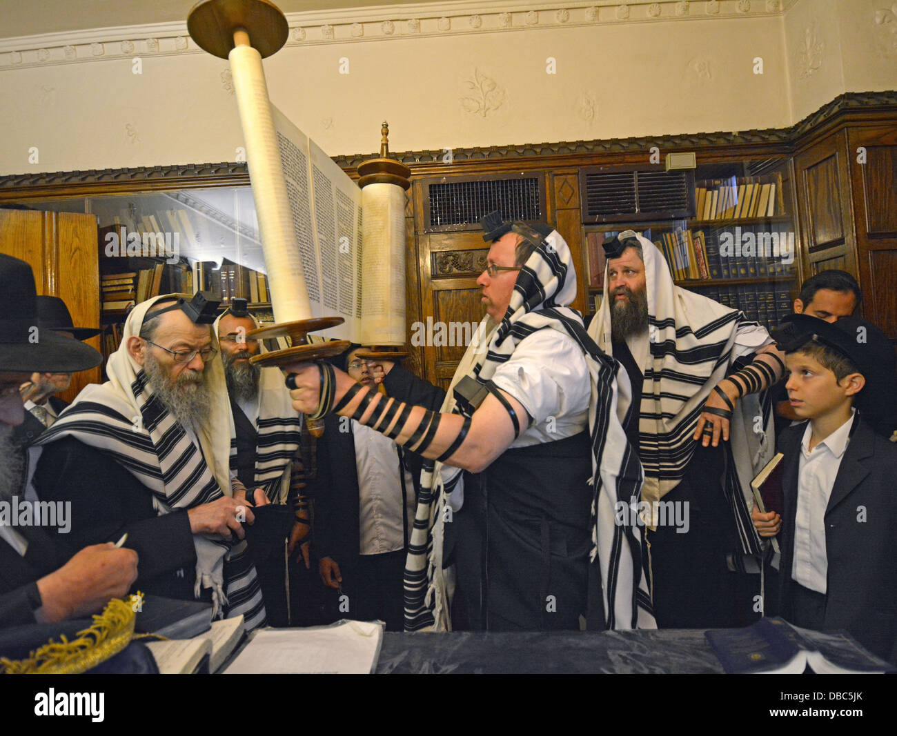 Thursday morning services in the Rebbe's study. The Torah being lifted prior to being closed and returned to - Stock Image