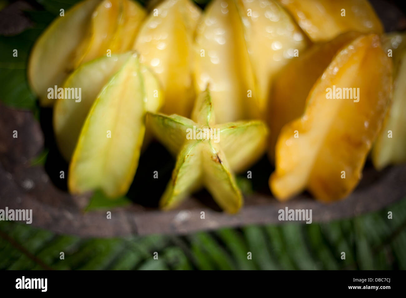 Star Fruit or Carambola in wooden bowl for sale at an organic fruit market in Aitutaki island, Cook Island - Stock Image
