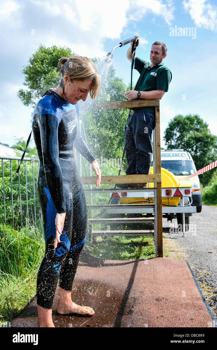 Dungannon, Northern Ireland, 28th July 2013 - A female competitor is hosed down after swimming at the 2013 Northern - Stock Image