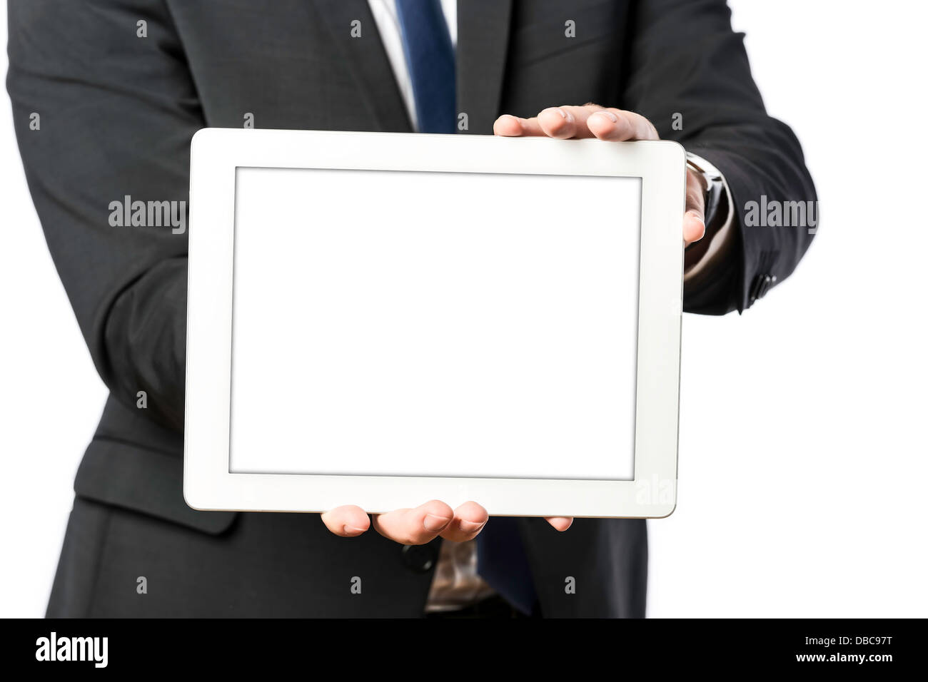 business man in dark suit holds a tablet computer, isolated on white background - Stock Image