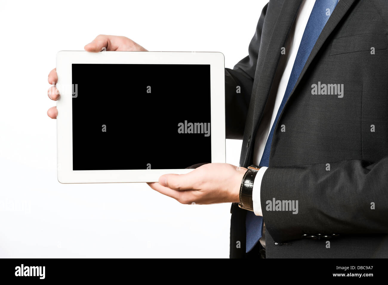 Business man in dark suit with blank tablet computer, isolated on white background - Stock Image