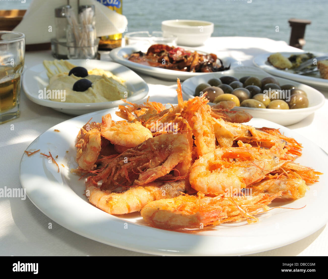 Waterside taverna table of  shrimps, squid in spicy tomato sauce, olives and houmous in lemon sauce,  Gikes,Peloponnese - Stock Image