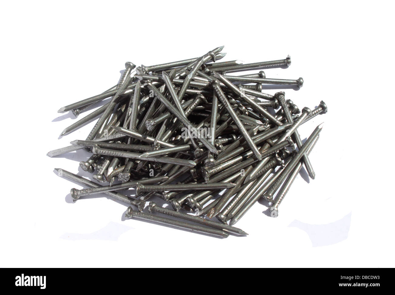 Bunch of 2 inches metal nails in white background - Stock Image