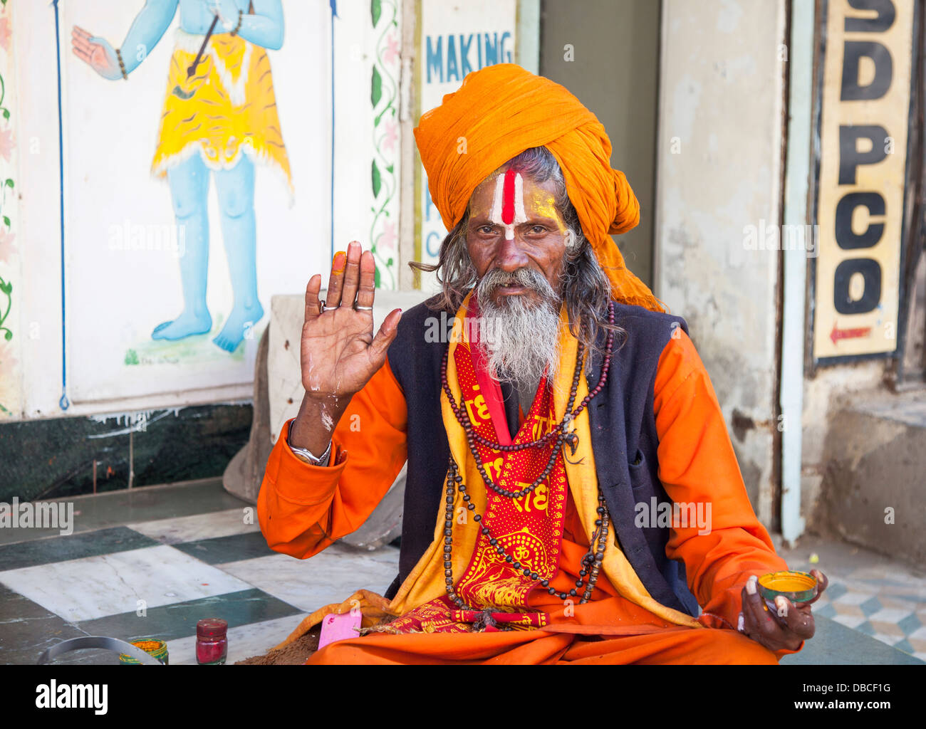 An elderly bearded Hindu sadhu, holy man, in traditional colourful saffron robes, giving a blessing in Udaipur, - Stock Image