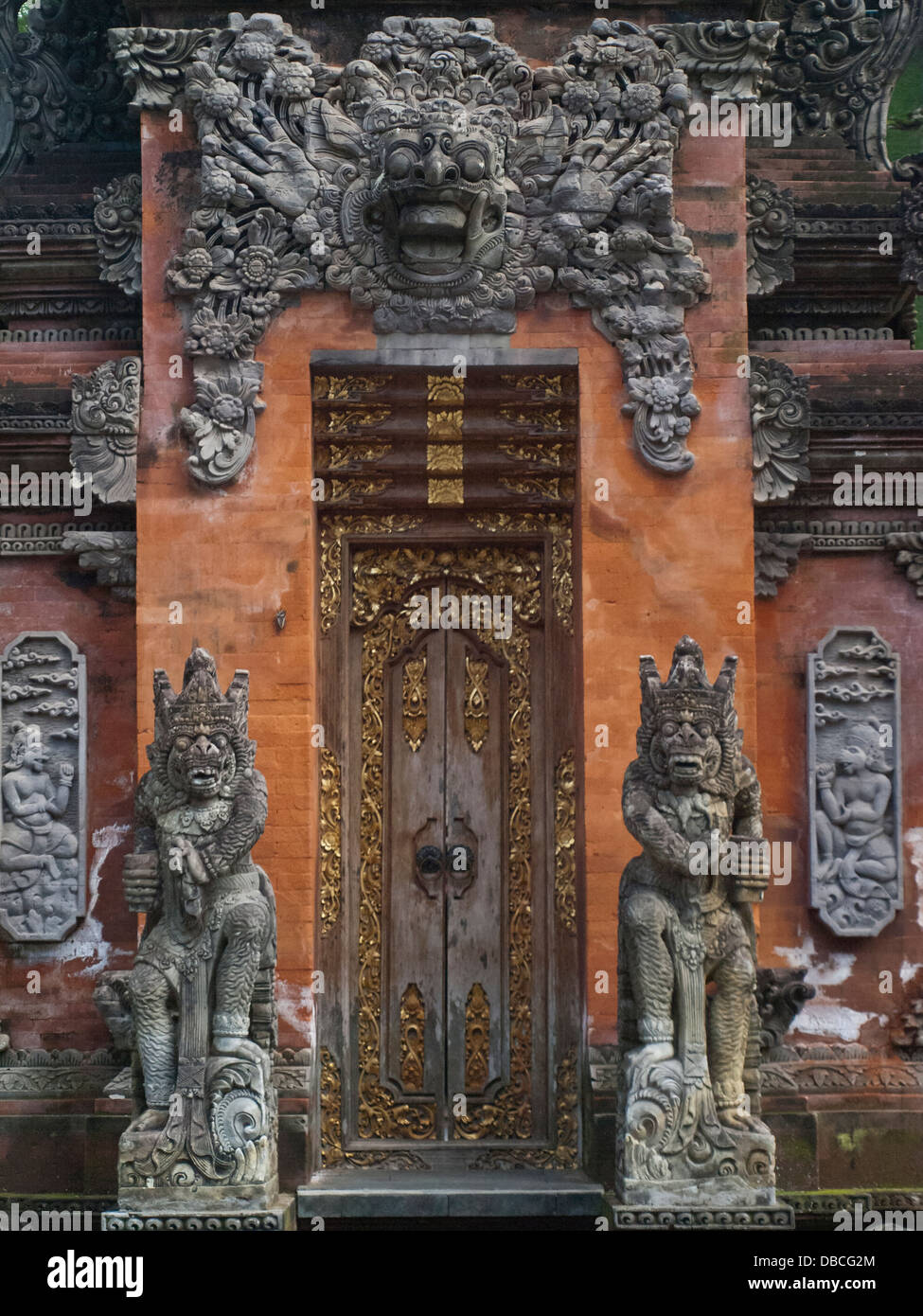 Bali temple door with traditional stone carvings stock photo