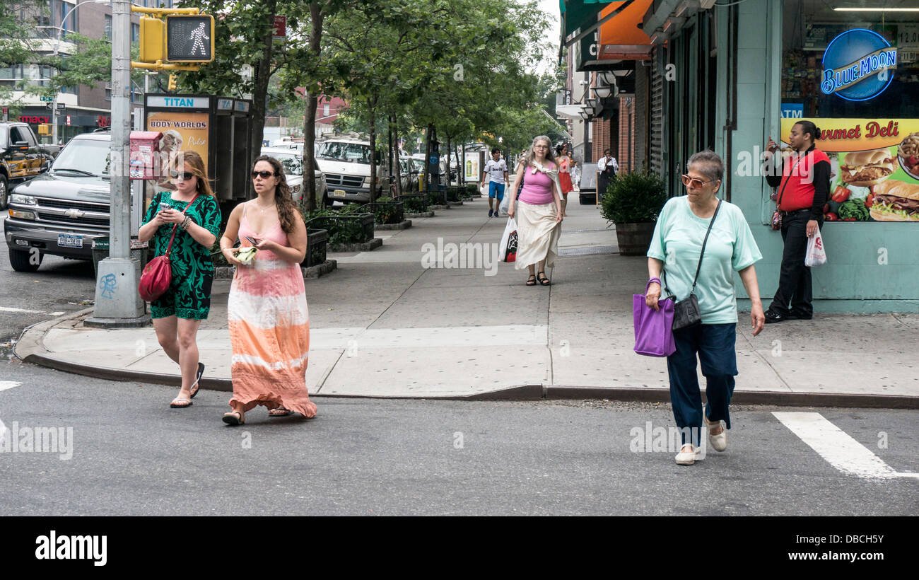 pedestrians on 9th Avenue on a beautiful summer day with several women wearing fashionable long skirts Hells Kitchen - Stock Image