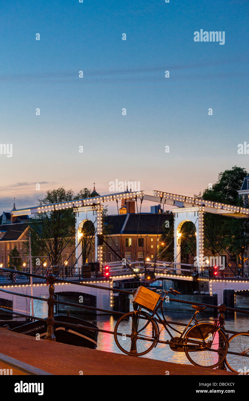 Amsterdam Magere Brug, Skinny Bridge, on the Amstel River and Hermitage Museum at dusk night evening in summer Parked - Stock Image