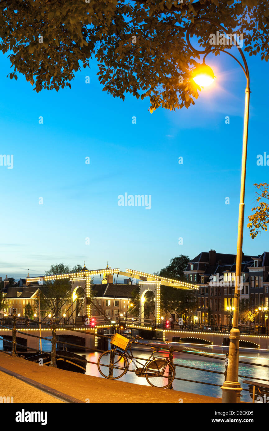 Amsterdam Magere Brug Skinny Bridge on the Amstel River dusk night evening in summer. A single bicycle is locked - Stock Image