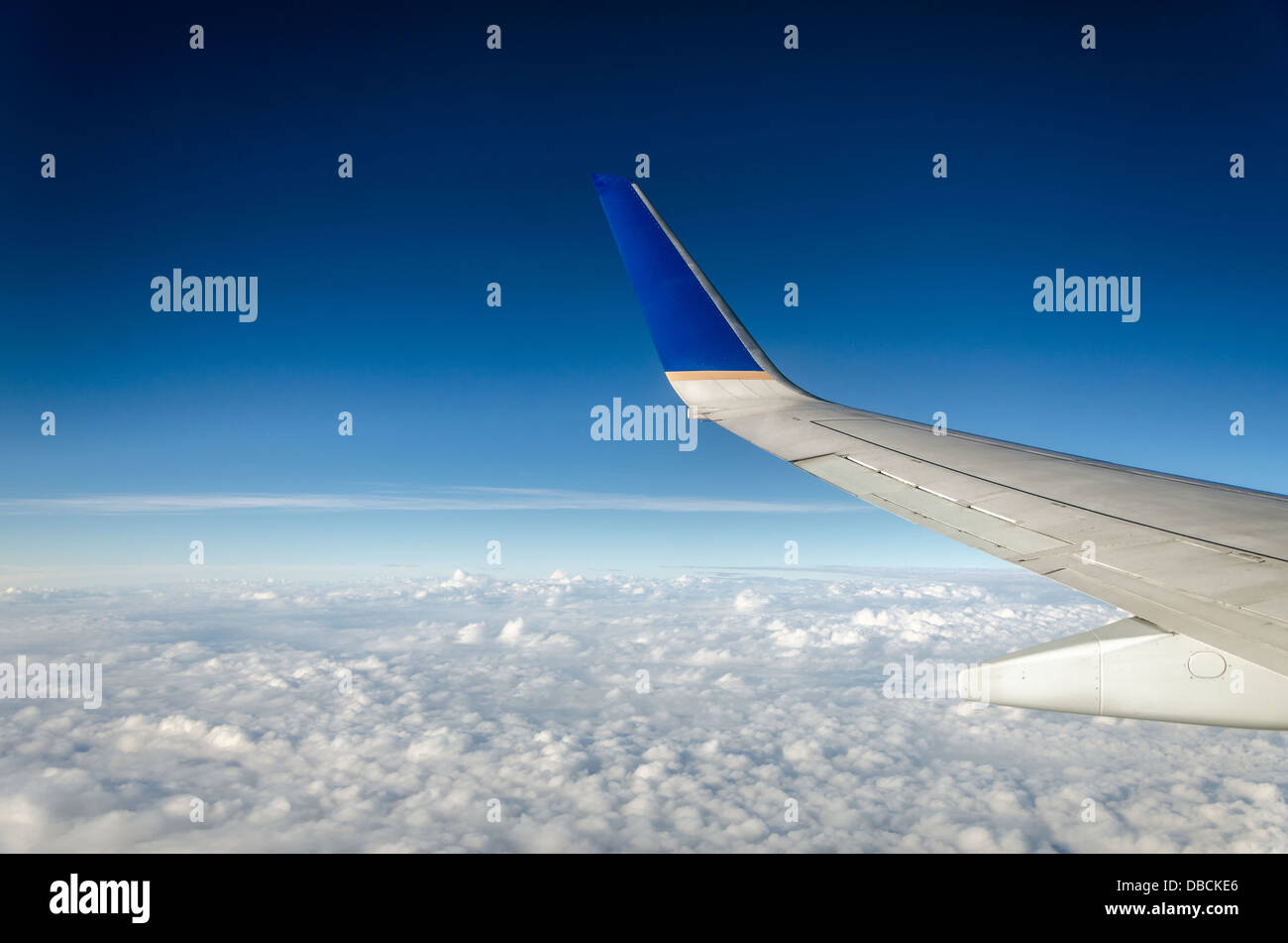 Wing of an airplane with beautiful white clouds and a deep blue sky - Stock Image