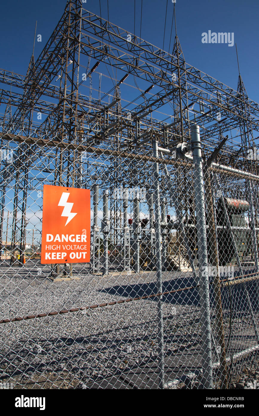 Danger - keep out sign on fence surrounding electrical substation - Stock Image
