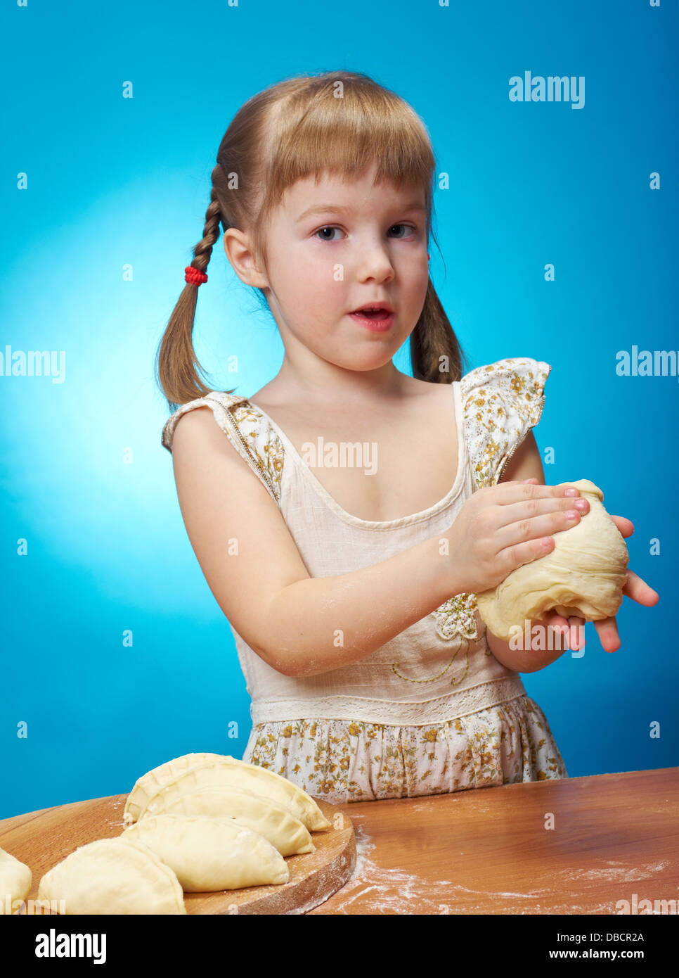 Smiling little girl kneading dough at kitchen with baking a pie ...