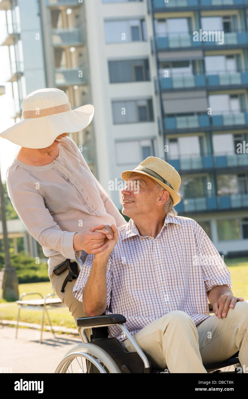 assistance,caucasian,cheerful,couple,crippled,disabled,elderly,female,handicapped,happy,holding hands,husband,invalid - Stock Image