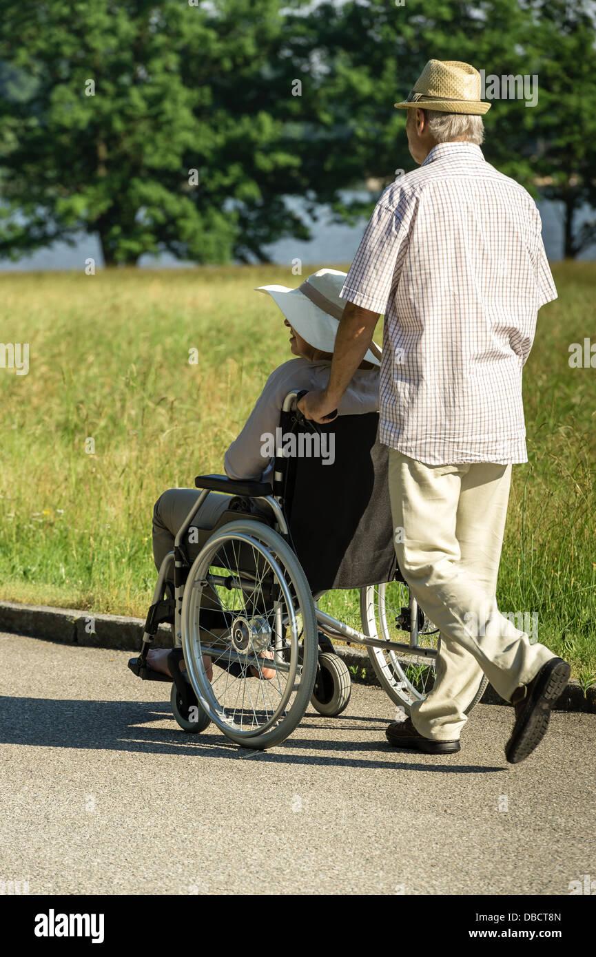 assistance,caucasian,couple,crippled,disabled,elderly,female,handicapped,husband,invalid chair,lifestyle,male,man,old,outdoors,paraplegic,pensioner,portrait,pushing,rehabilitation,retired,senior,senior - Stock Image