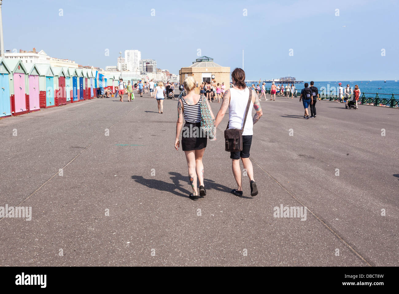 Pedestrians strolling along the seafront, Brighton, England, UK - Stock Image