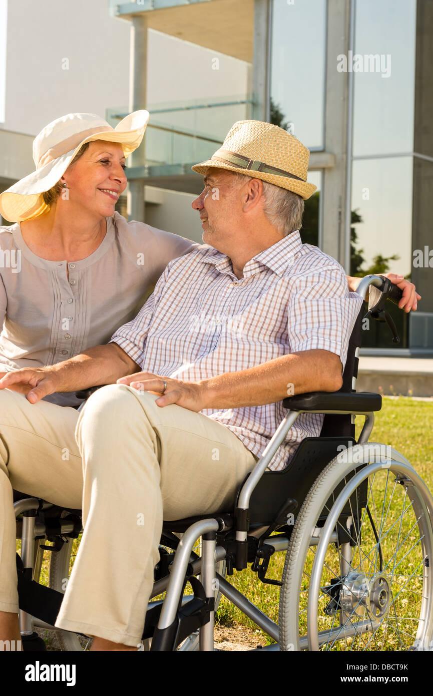 assistance,caucasian,cheerful,couple,crippled,disabled,elderly,female,handicapped,happy,husband,invalid chair,joyful,lifestyle,male,man,outdoors,paraplegic,pensioner,portrait,rehabilitation,relaxing,resting,retired,senior,senior - Stock Image