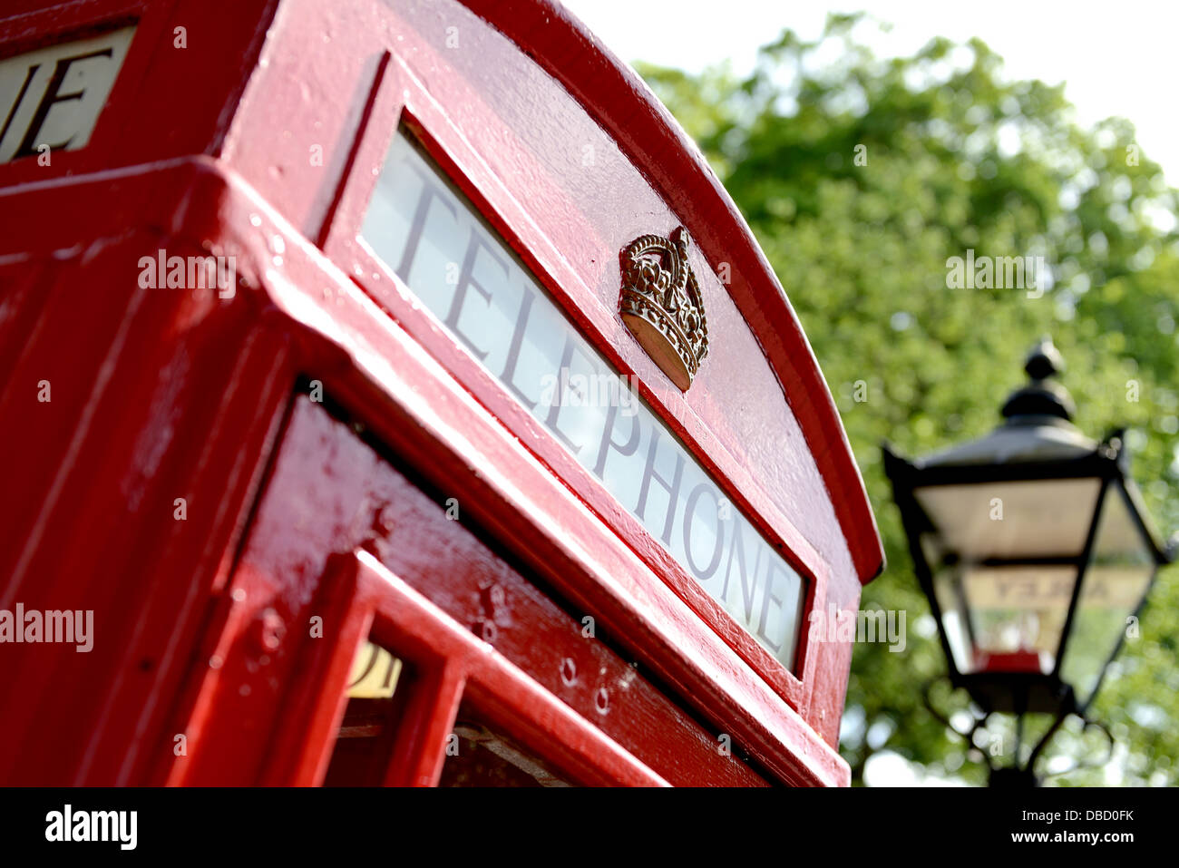 red telephone box with old fashioned london street light in soft focus - Stock Image
