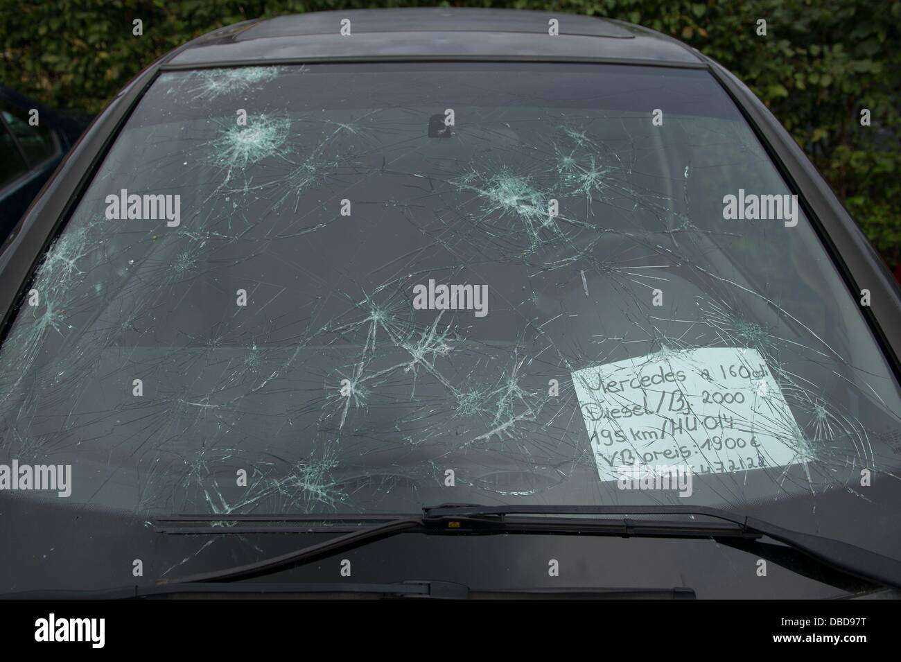 A car with a broken front window destroyed by hail stands at a car ...