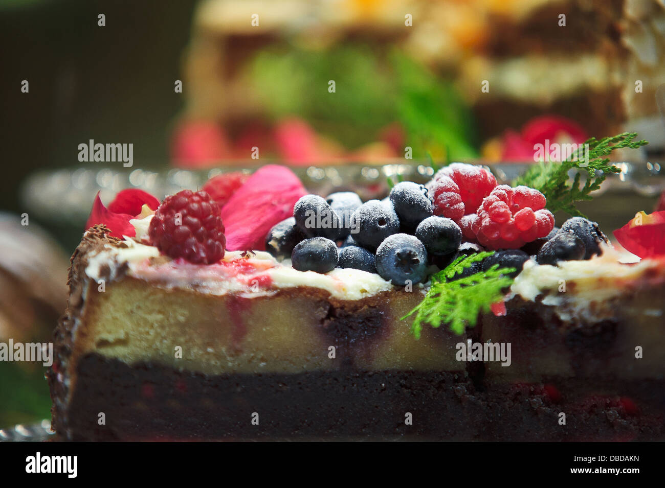 A baked cheesecake topped with cream and berries ready to eat - Stock Image