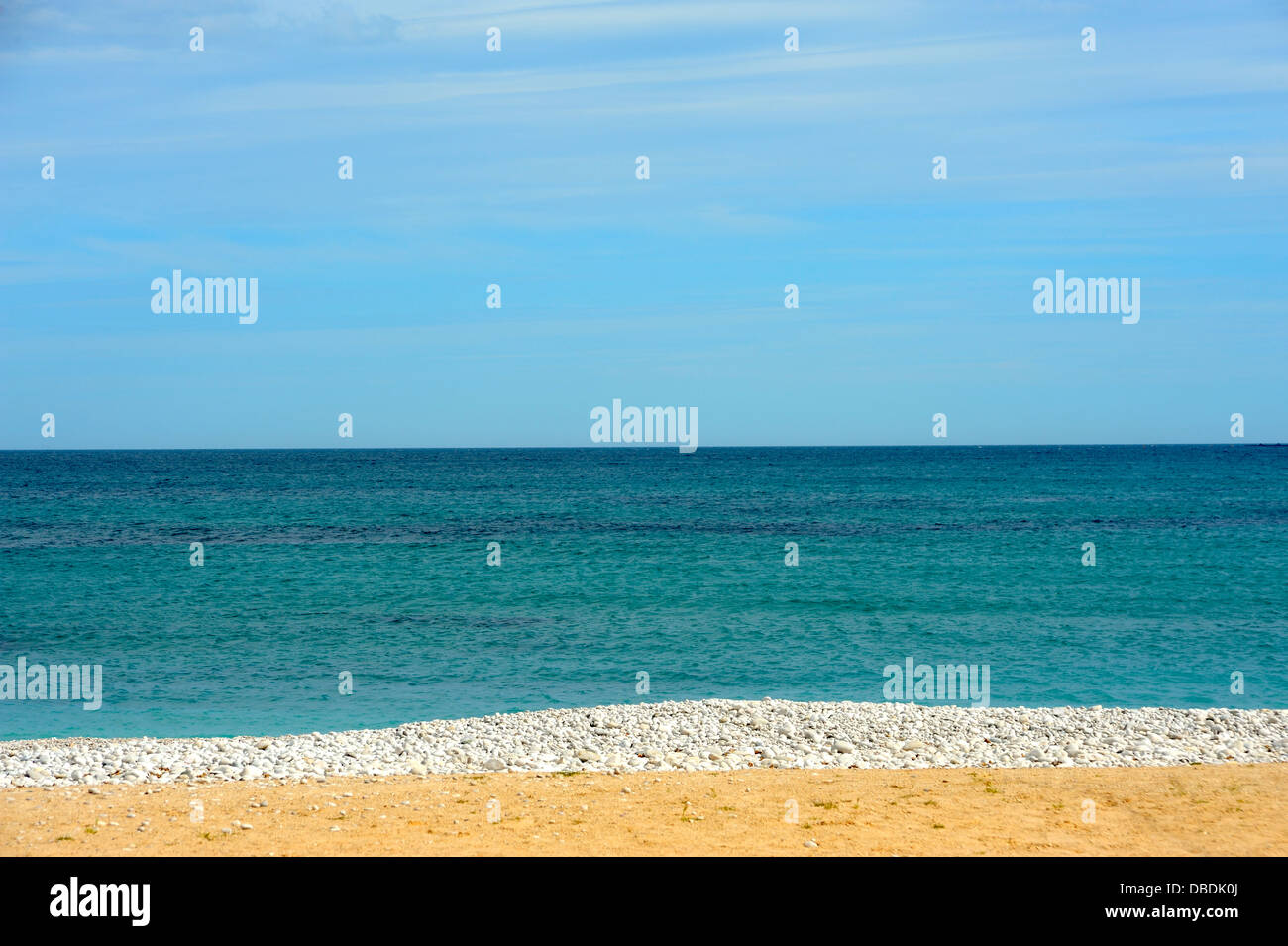 SAND PEBBLES SEA SKY BEACH  IN SPAIN - Stock Image