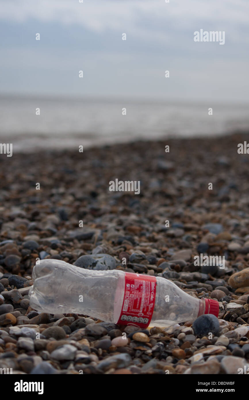 Litter on the rocky stone beach showing a empty discarded Coca Cola bottle. - Stock Image