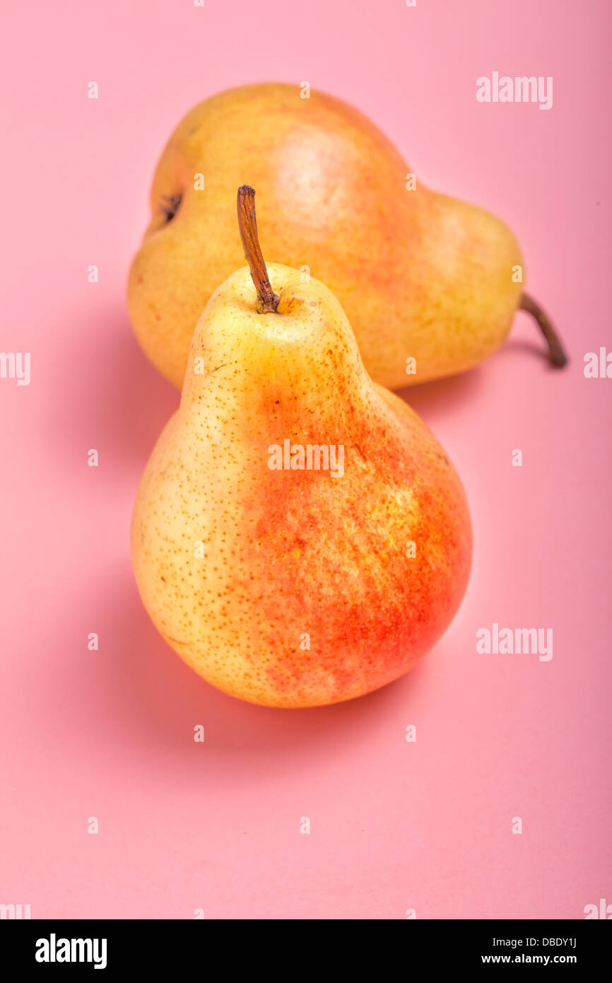 Fresh ripe Bartlett Pears on a pink background. - Stock Image