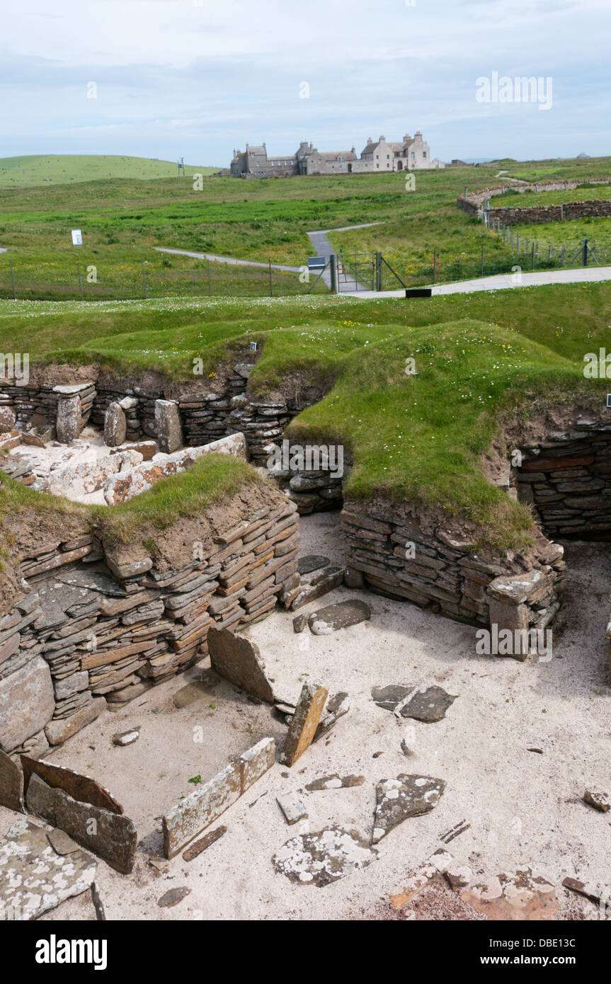 House 5 at Skara Brae Neolithic Village on Mainland Orkney with Skaill House in the background. Stock Photo