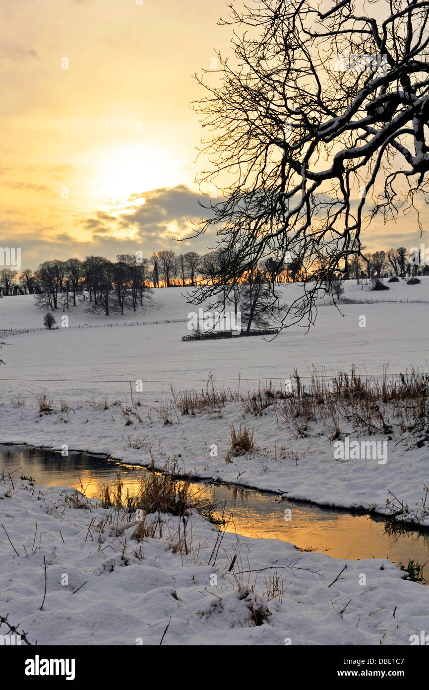 Snowy fields and stream at sunset, Meon Valley, Hampshire, England, UK, Western Europe. - Stock Image