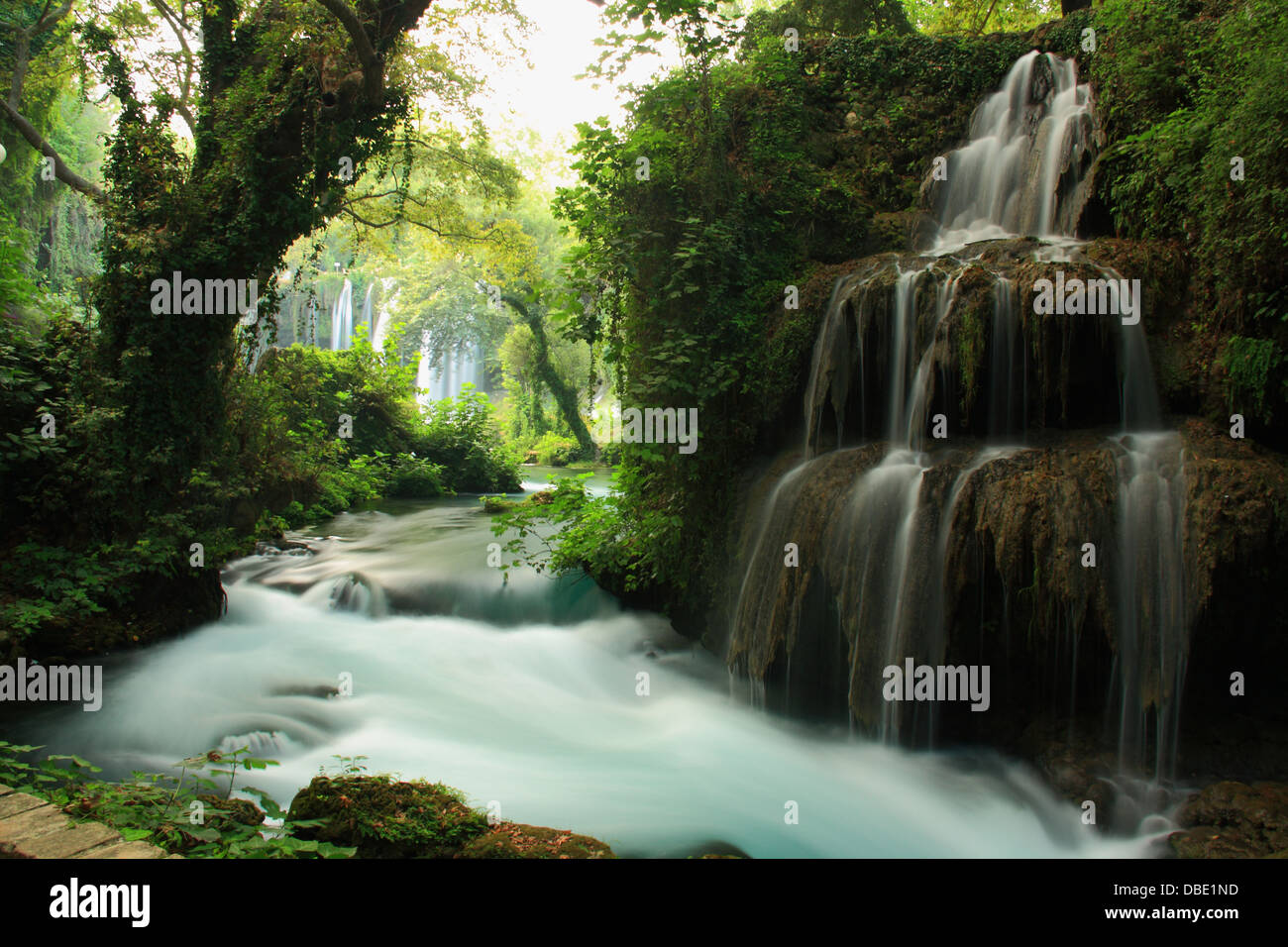 tourquoise stream landscape in forest with view of big waterfall - Stock Image