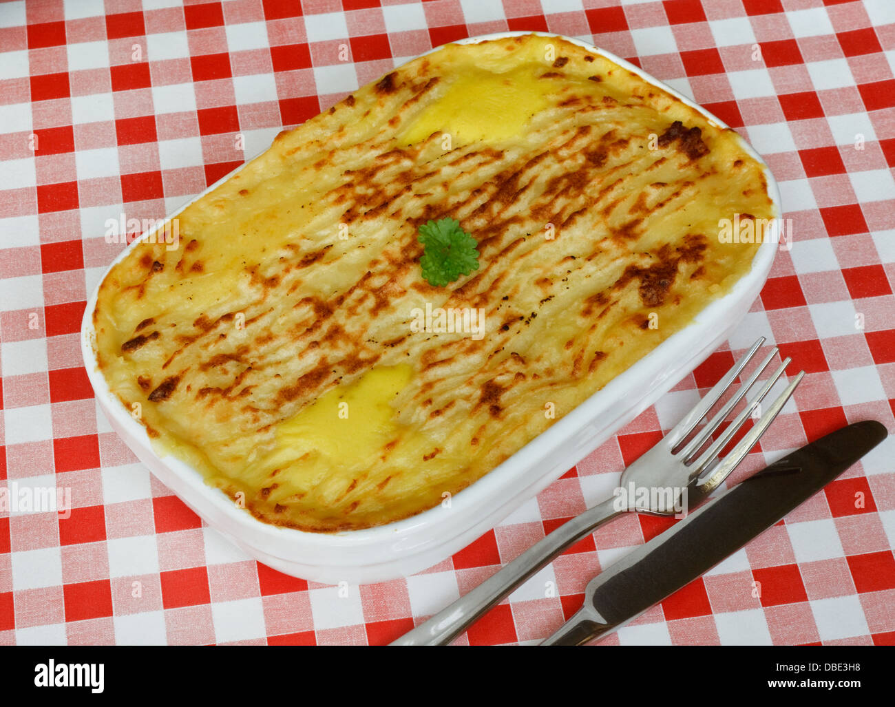 Traditional Homemade Fish Pie in a casserole dish with crispy mashed potato on the top on a red gingham tablecloth - Stock Image