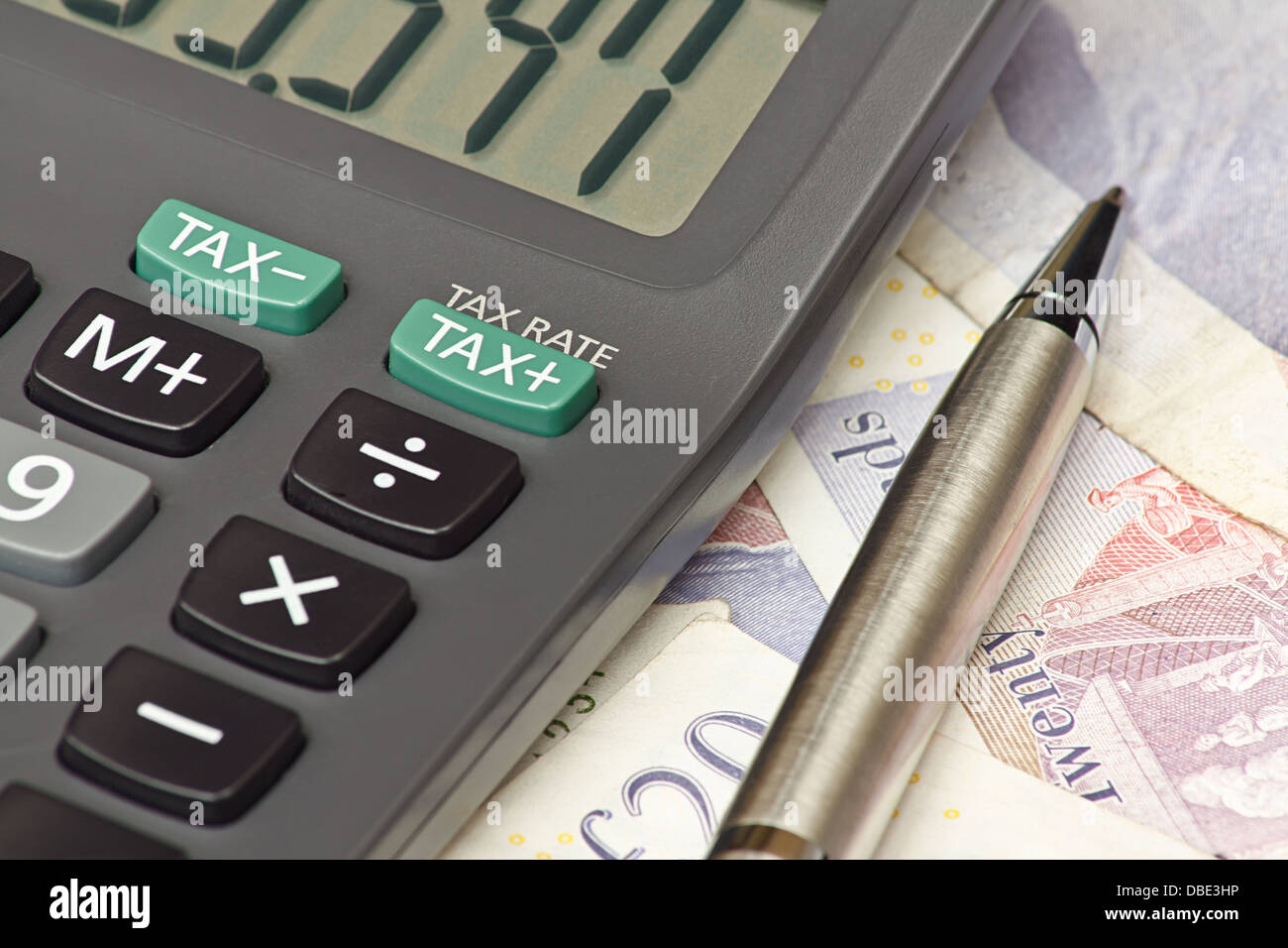Calculator and pen symbolizing completing your personal Income tax returns for the inland revenue service or IRS - Stock Image