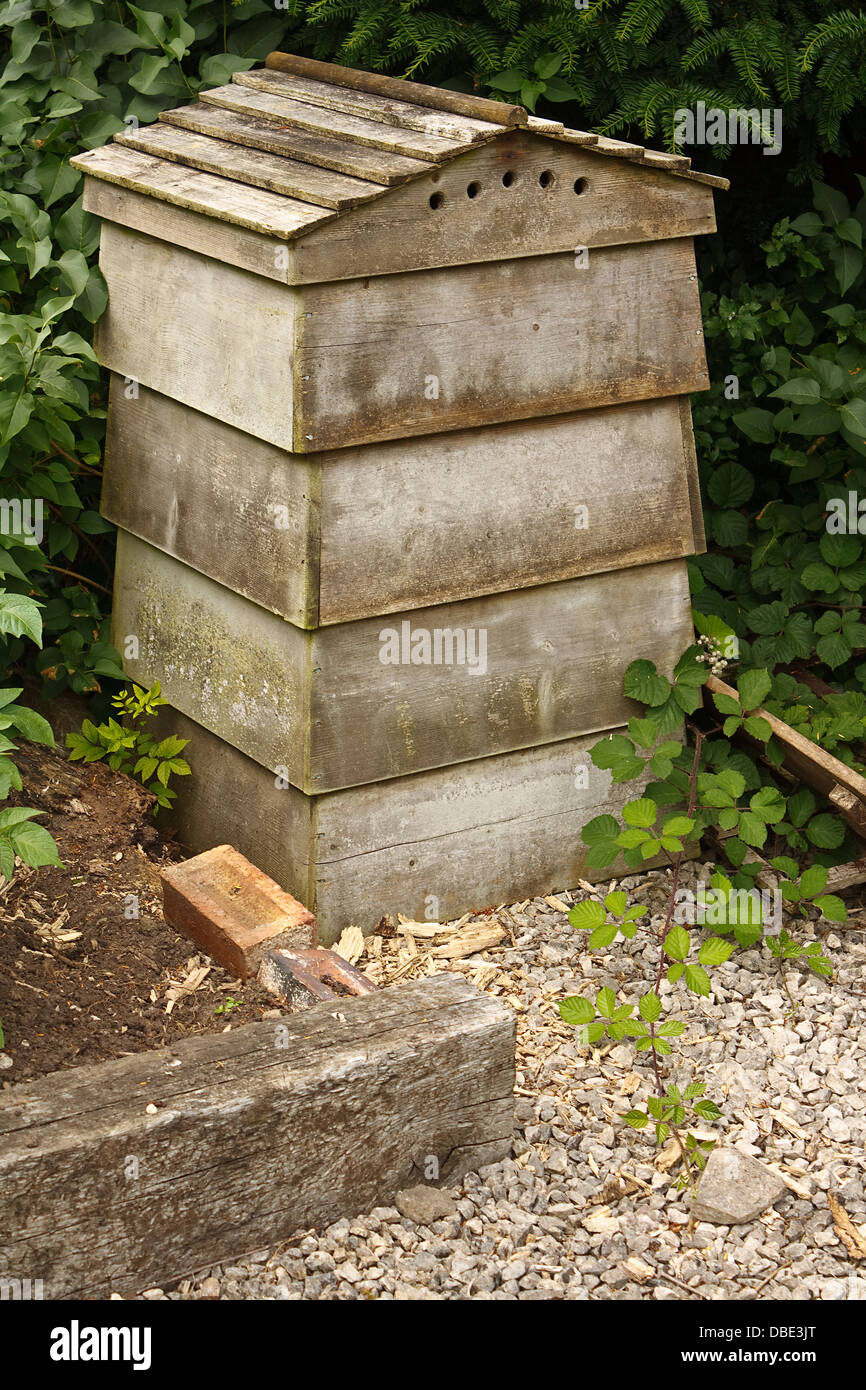 Wooden beehive a home for bees who pollinate local trees and flowers whilst producing honey which is collected by - Stock Image