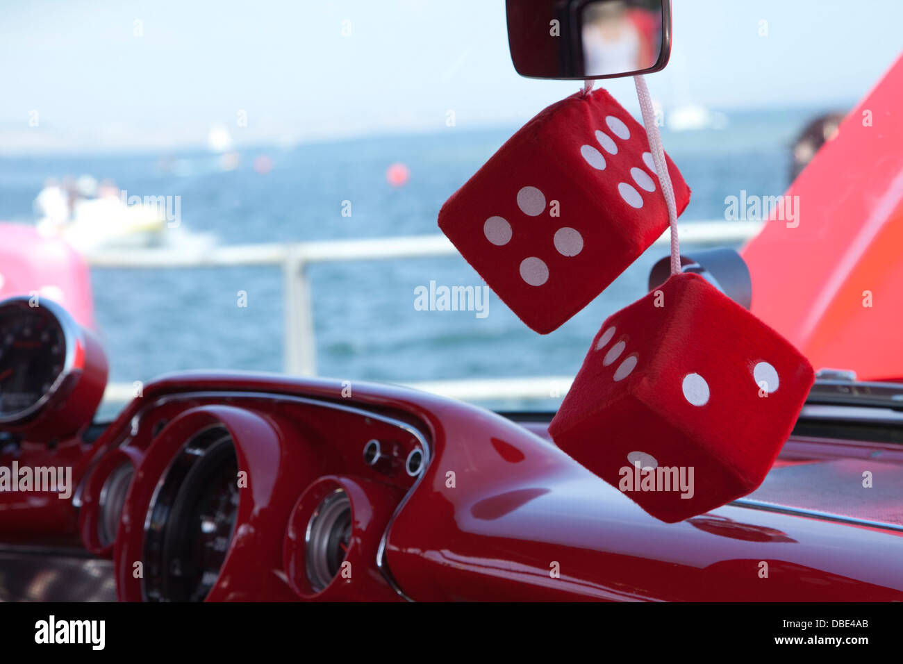 Fluffy red dice on a dash board - Stock Image
