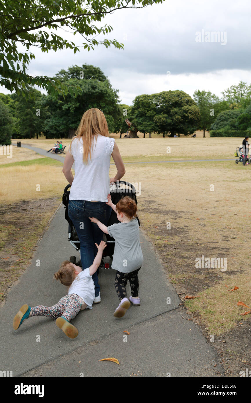 Young mum with twin girls and one is having a temper tantrum. - Stock Image