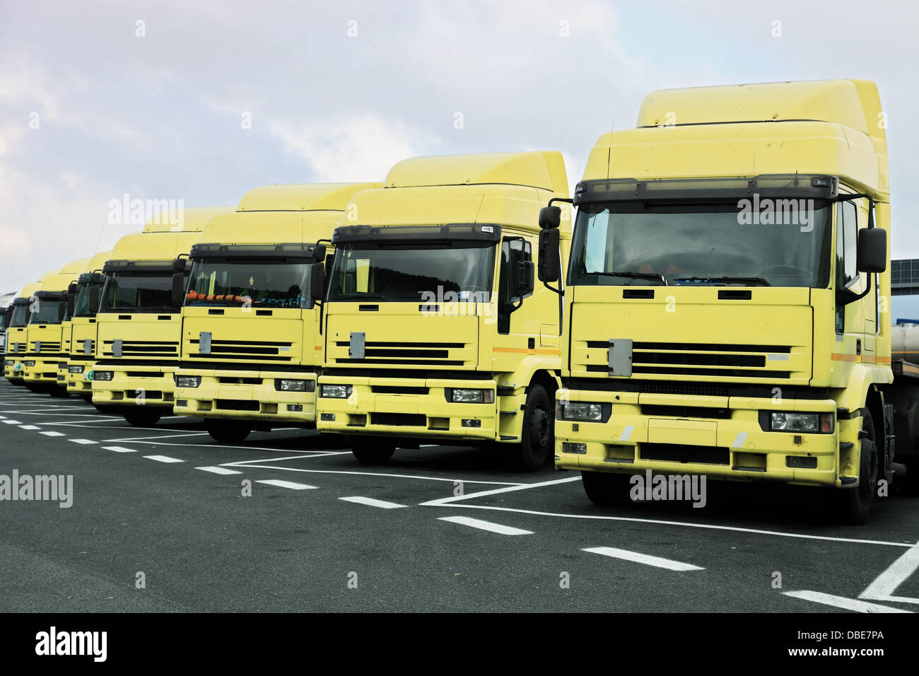 many big yellow trucks parked in line - Stock Image