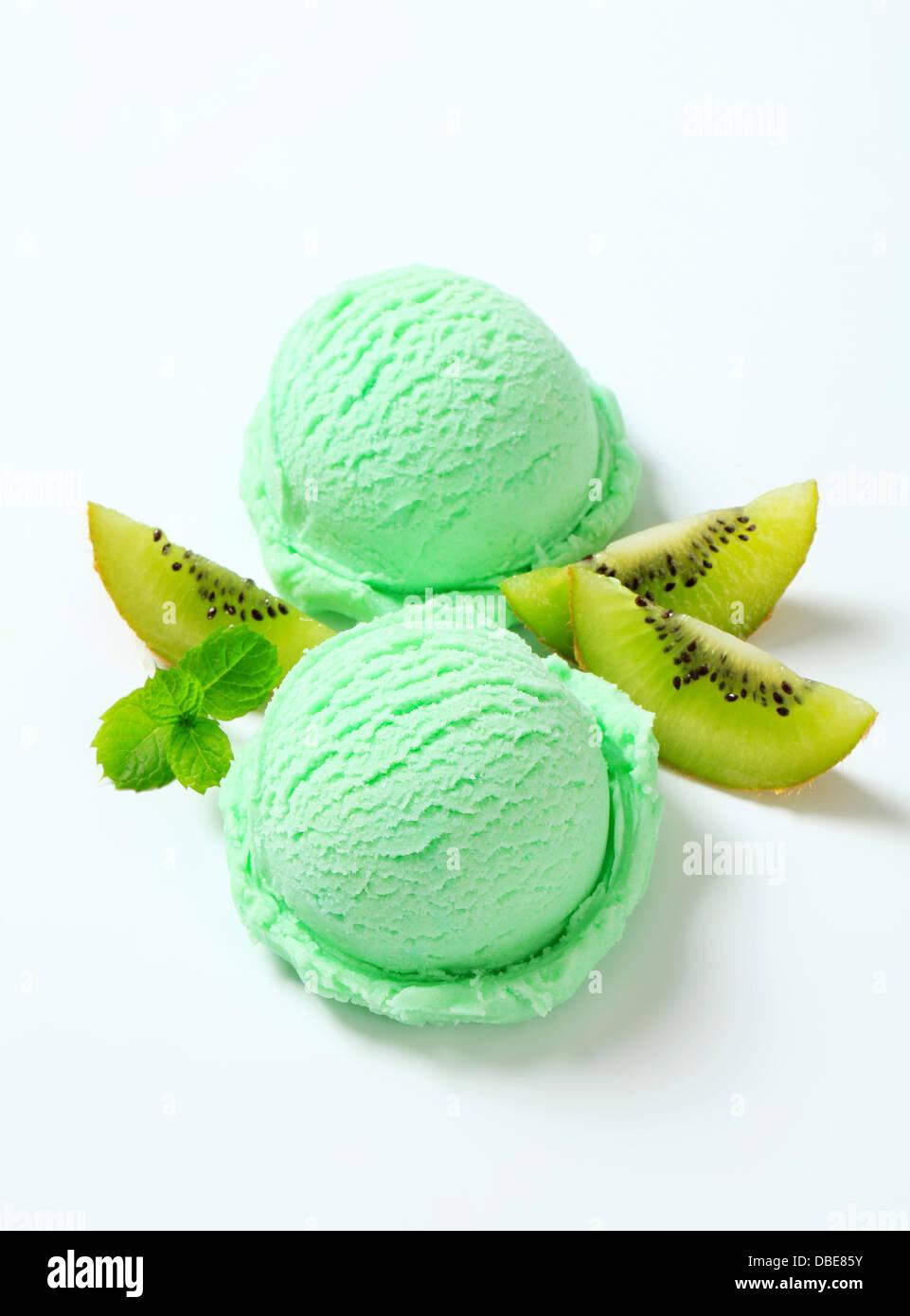 Scoops of light green ice cream and fresh kiwi - Stock Image