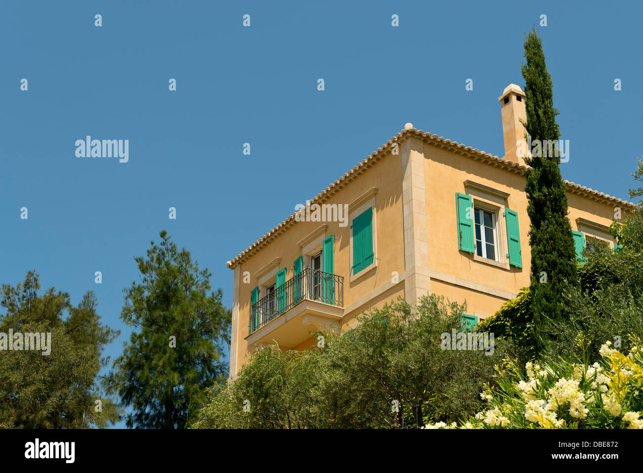 Sandy coloured house with green shutters on the Ionian Island of Kefalonia, Greece - Stock Image
