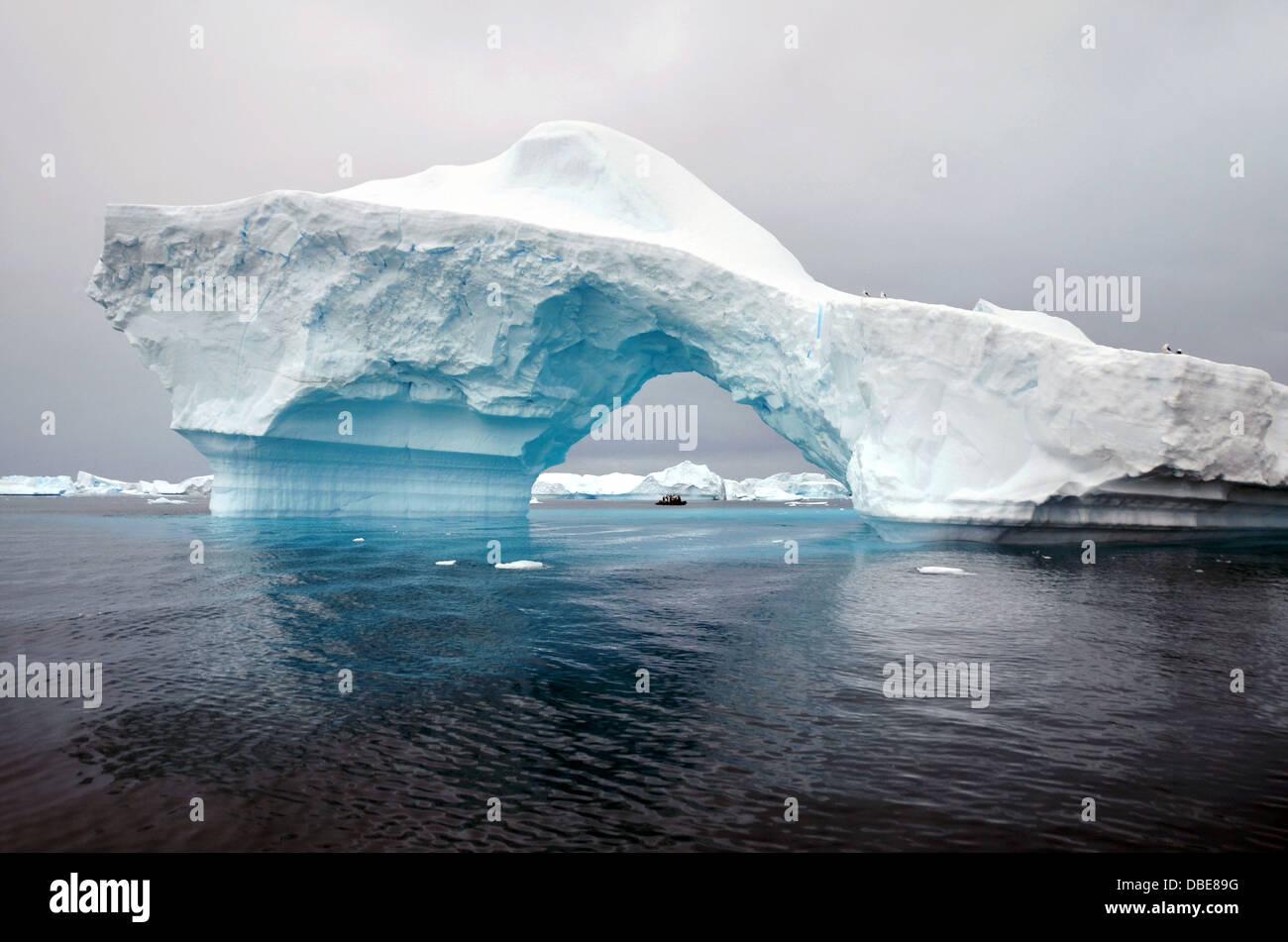 A zodiac boat cruises through an opening in a beautiful ice berg near Pleneau Islands, Antarctica - Stock Image