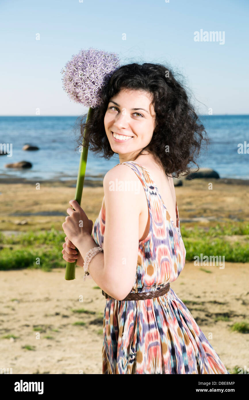 Young woman with dark hairs hold lilac flower - Stock Image