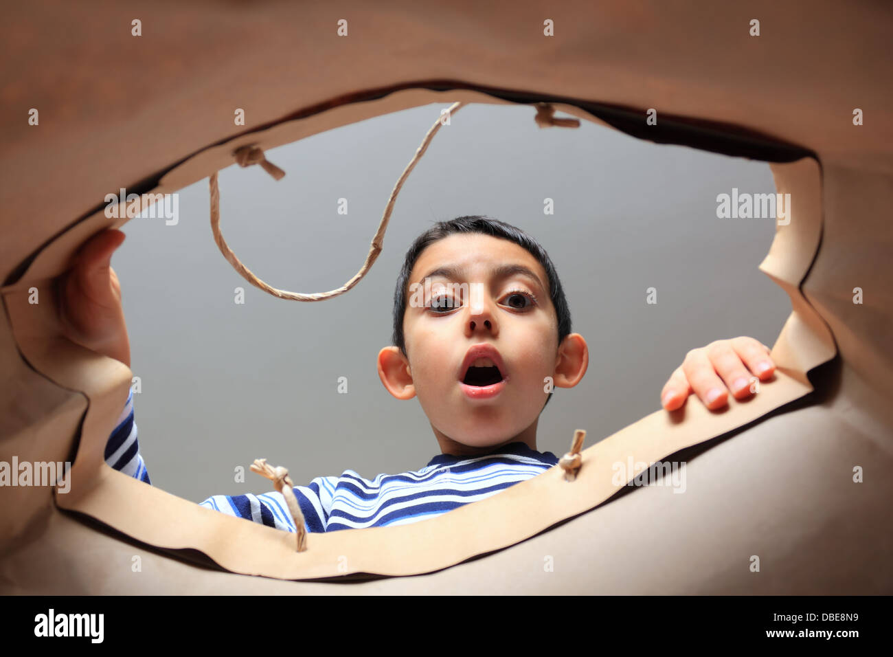 child opening bag and looking inside with surprise - Stock Image