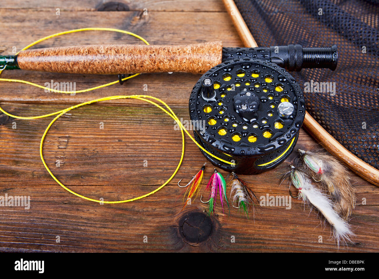 fly fishing rod and reel on a wet wooden background, focus on the reel. - Stock Image