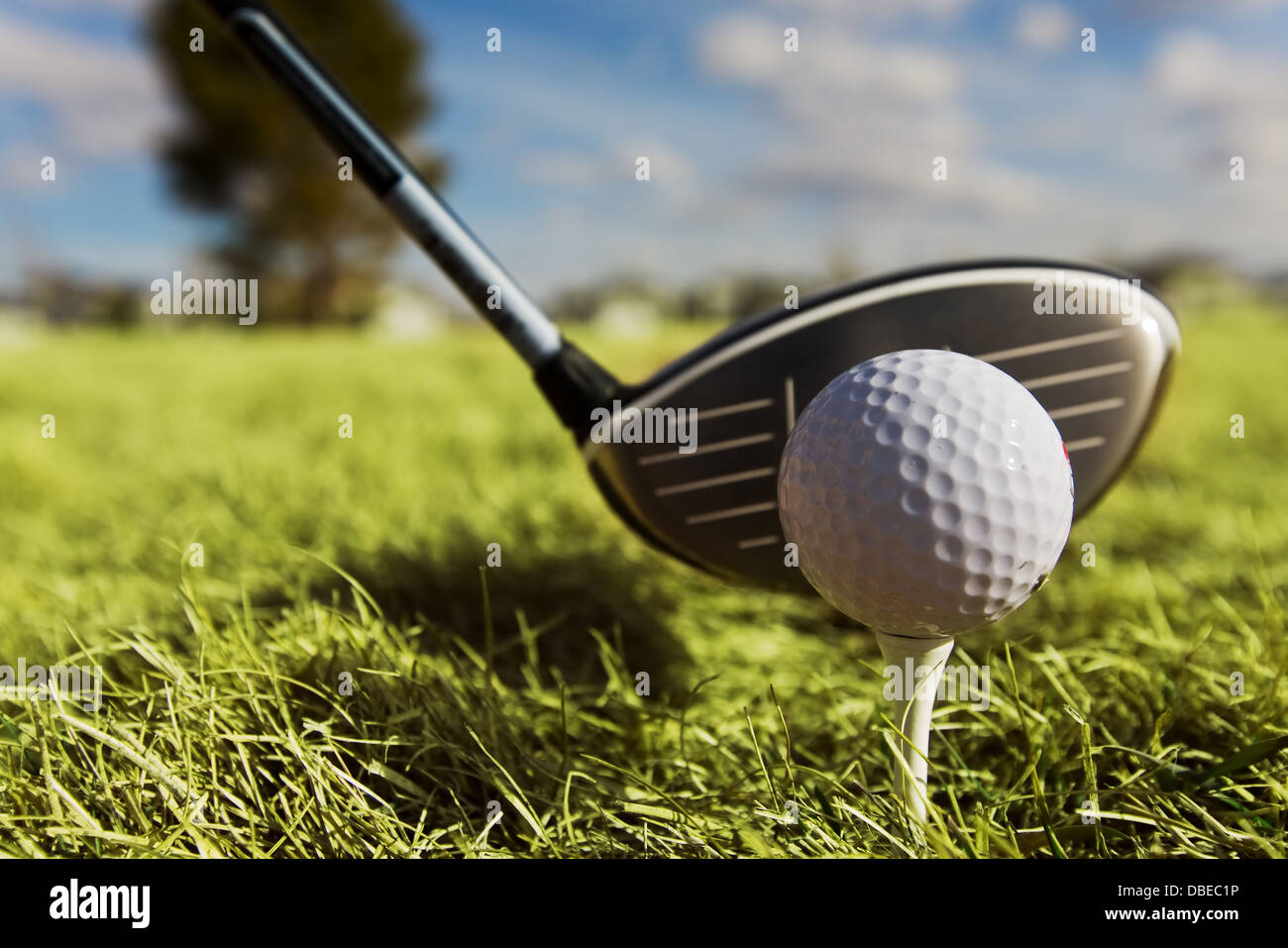 A golf ball and left handed driver with main focus on the ball. - Stock Image