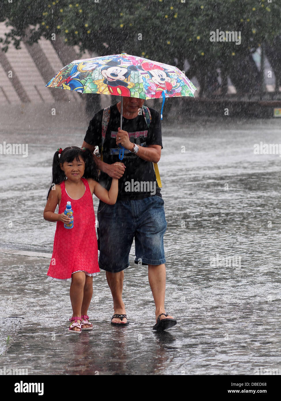 Father and daughter sheltering under their umbrella during a downpour of rain in Hong Kong - Stock Image
