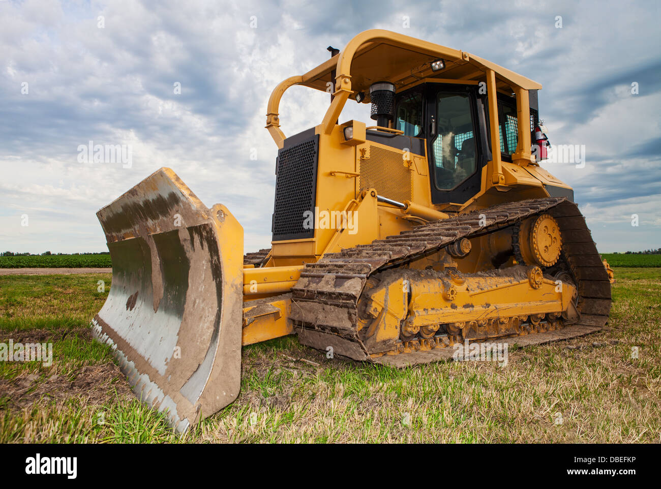 A large yellow bulldozer on a construction site near a farmers field - Stock Image