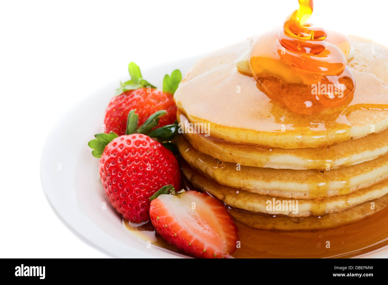 Pancakes and strawberry with maple syrup poured on top - Stock Image