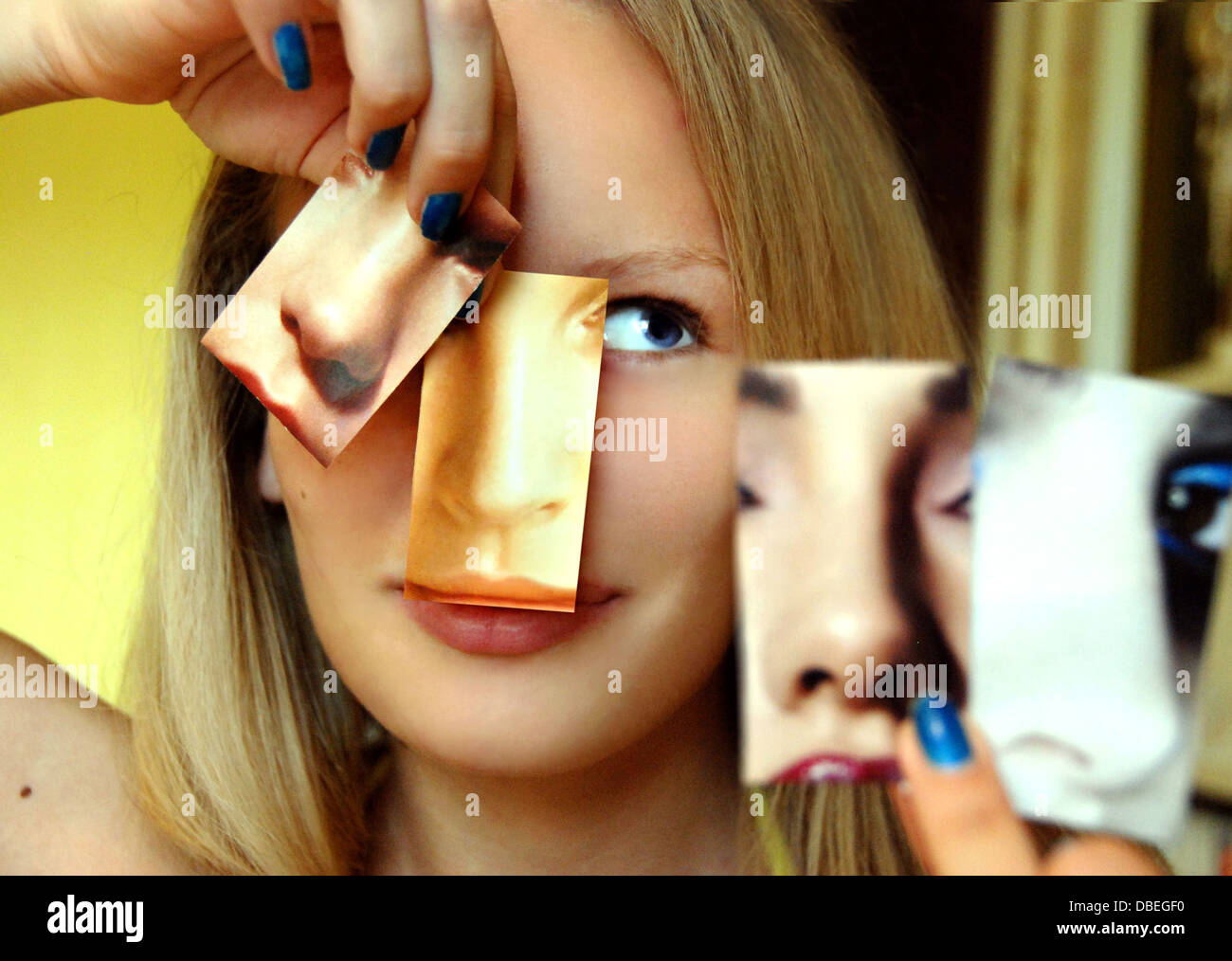 Pick Your Nose, a woman picks out her favorite nose among magazine cutouts for a nose job plastic surgery - Stock Image