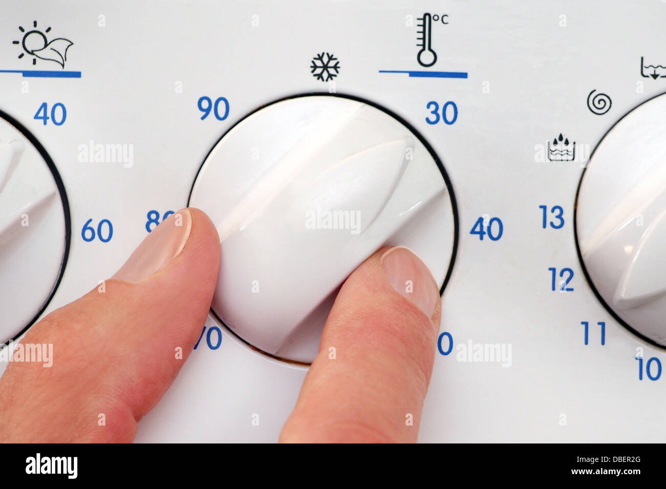 Person adjusting temperature dial of a washing machine - Stock Image